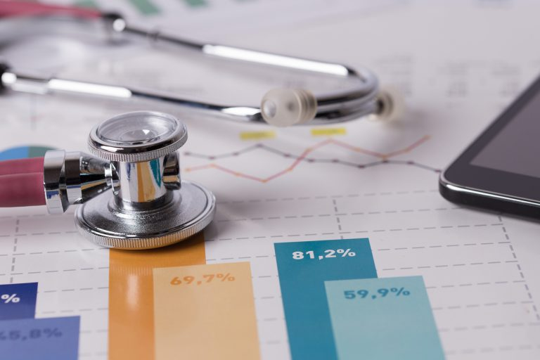 Stethoscope on top of medical billing papers